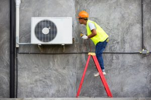Technician checking air conditioner on the wall