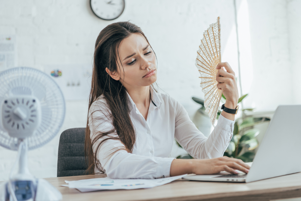 Exhausted businesswoman using laptop while conditioning air with electric fan and hand fan in office.