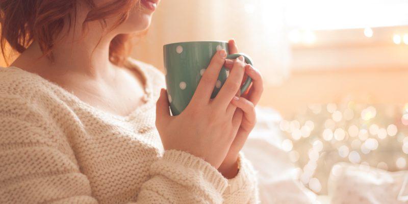 Woman drinks hot drink in mug while enjoying heated room.