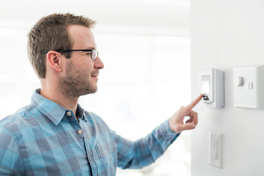 Businessperson Setting Temperature On Digital Thermostat Attached To Wall.