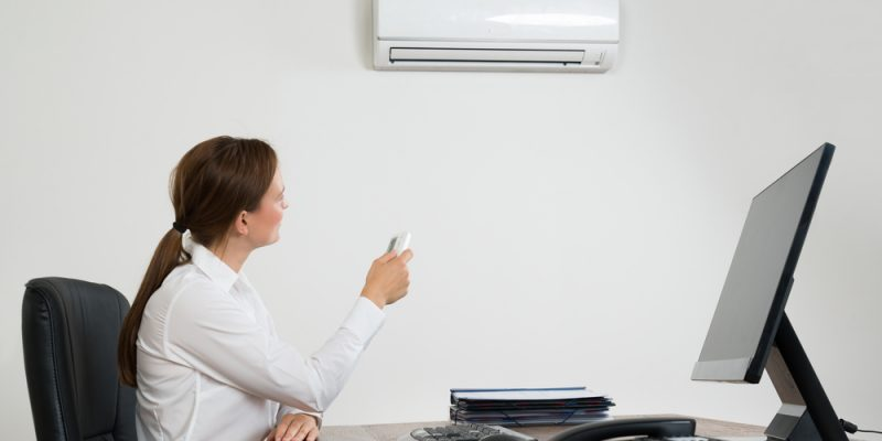 Businesswoman Sitting On Chair Using Air Conditioner In Office.
