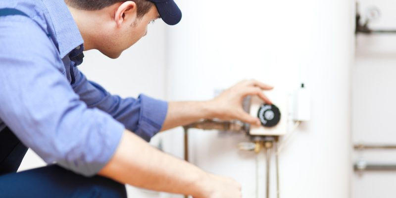 Technician servicing the gas boiler for hot water and heating.